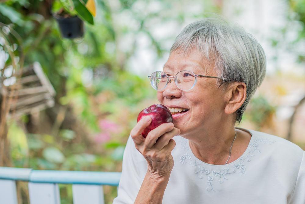 Elder lady with dental implants eating an apple