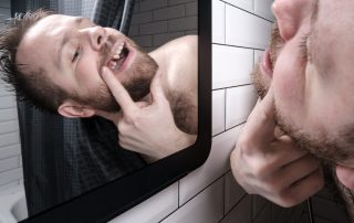 Man opened his mouth and carefully examines the absence of a tooth in mirror